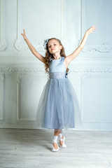 A little adorable young ballerina in a playful mood in the inter
