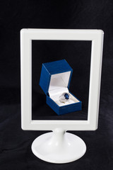 Box of ring behind white frame