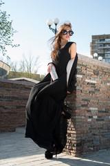 woman standing near a brick wall