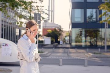 Junge Frau telefoniert mit ihrem Handy auf der Straße