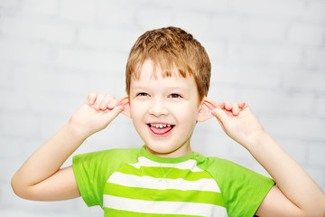 Happy little boy, pulling himself on the ears  and stuck out his