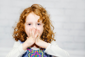 Little girl covering her mouth with her hands. Surprised or scar