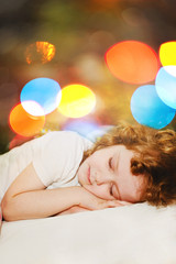 Little girl is sleeping. Against the background of the rainbow b