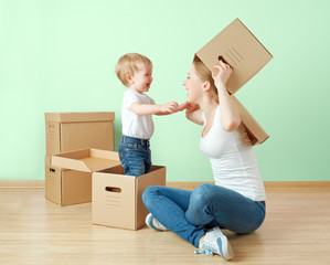 happy family mother and baby daughter in apartment with boxes