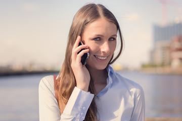 Attraktive Frau führt ein Gespräch mit ihrem Handy