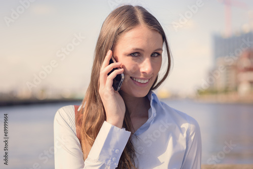 canvas print picture Attraktive Frau führt ein Gespräch mit ihrem Handy
