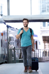 Happy young man walking with suitcase at train station