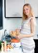 Happy pregnant housewife cooking