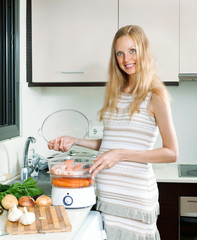 Happy pregnant woman cooking