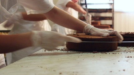 Chefs cutting chocolate cake into layers and stacking them.