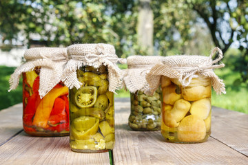 Jars of preserves on wooden table in the garden