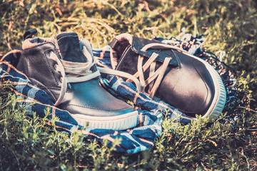 men's shoes on the grass wrapped in a scarf