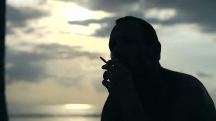 Man smoking cigarette at the seaside, slow motion 240fps