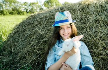 teen girl with white rabbit sitting in front of haystack