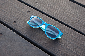 blue plastic sunglasses and wooden floor