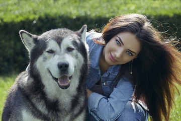 Beautiful smiling woman with Malamute male dog