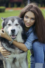 Beautiful happy woman hugging big Malamute male dog