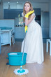 Woman Wearing Gown Mopping Floor in Kitchen