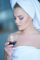Woman in Bath Towel Looking Down at Glass of Wine