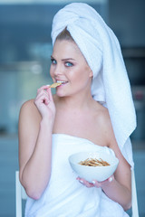 Woman in Bath Towel Eating Snacks from Bowl
