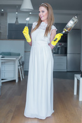Woman Wearing Wedding Gown Holding Pan in Kitchen