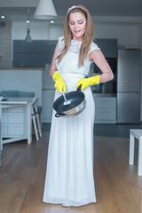 Woman Wearing Wedding Gown Washing Pan in Kitchen