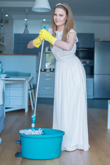 Woman Wearing Wedding Gown with Mop and Bucket