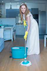 Woman Wearing Wedding Gown Mopping Floor