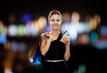 smiling woman with shopping bags and credit card
