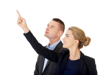 Successful business couple pointing away