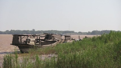 Old  boats moored at the bank of mekong. The wind blow strongly