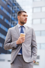 young serious businessman with paper cup outdoors