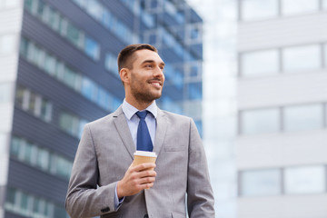 young smiling businessman with paper cup outdoors