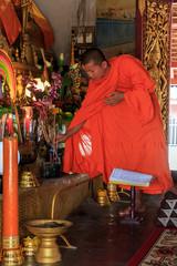Young Buddhist Monk puts incense sticks