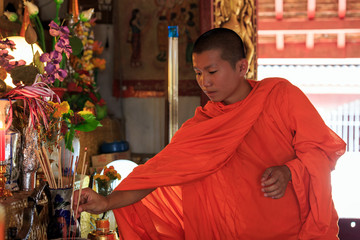 Young Buddhist Monk puts incense sticks