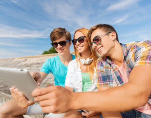 group of smiling friends with tablet pc outdoors