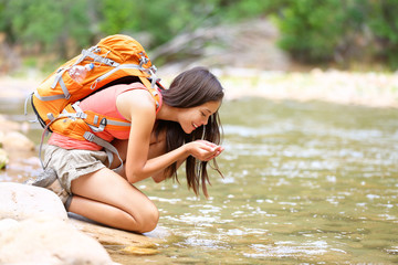 Hiker woman drinking water from river creek hiking
