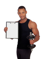 Handsome muscled man training with dumbbells and clipboard in bl