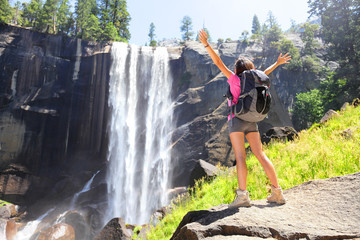 Hiking woman freedom in Yosemite park by waterfall