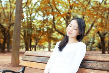 公園のベンチで休む女性