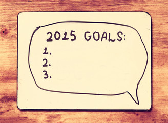 vintage board with phrase 2015 goals over wooden table. retro vi