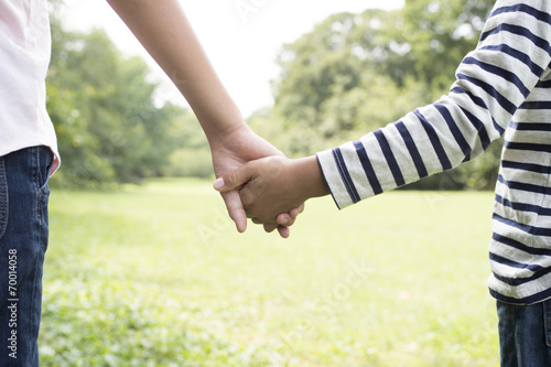 Poster Holding Hands siblings in the grass