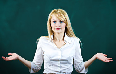 Clueless, unhappy young blonde woman on green background