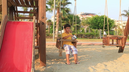 Boy eating chips on swing