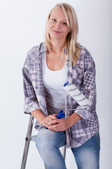 Young beautiful woman with paint roller