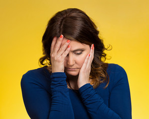 Depressed stressed thoughtful young woman yellow background