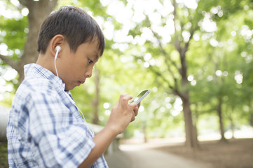 Boy listening to music from a mobile phone in the park