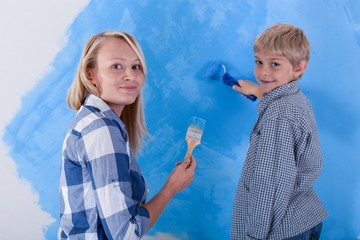 Son and his young mother painting the new apartment