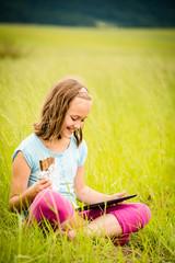 Girl enjoying chocolate and watching tablet