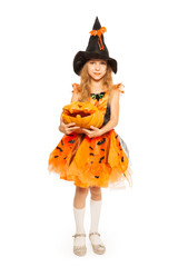 Girl in witch dress hold carved Halloween pumpkin
